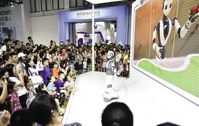 观众在参观展出的智能机器人进行舞蹈表演.jpeg